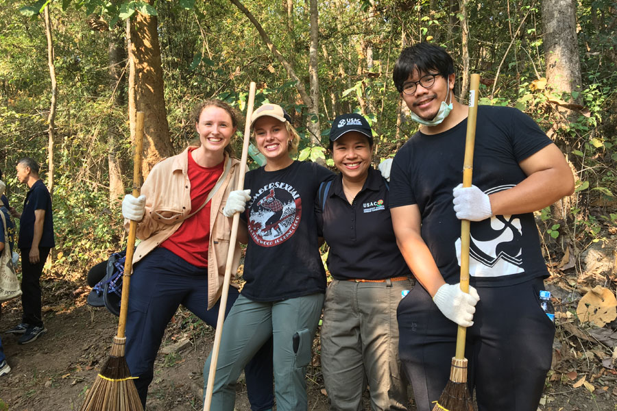 USAC students and the Resident Director, Jum, pose for a photo during volunteer activity to build a firebreak in Chiang Mai, Thailand