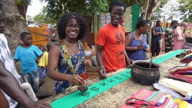 Students in Ghana learn local stamping during a group activity for study abroad
