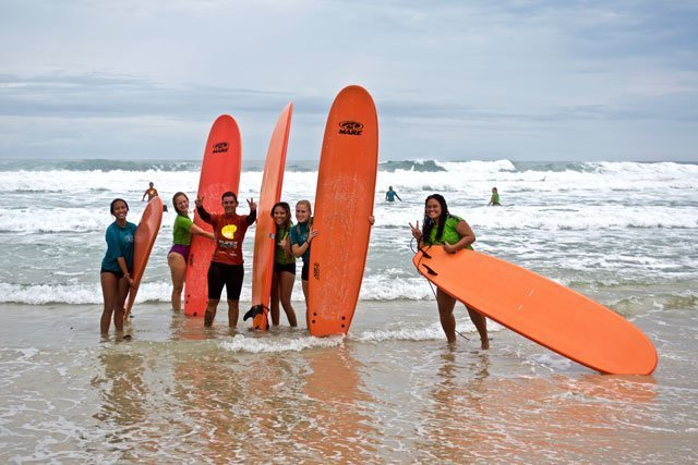 A group of students learn to surf during an education abroad experience with USAC