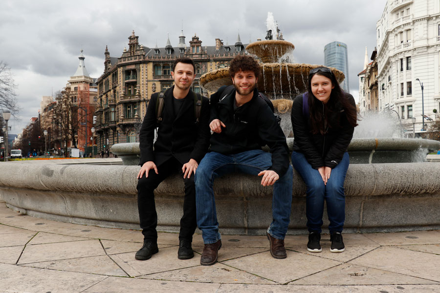 USAC Bilbao students sit in front of a fountain in the city of Bilbao during a semester study abroad