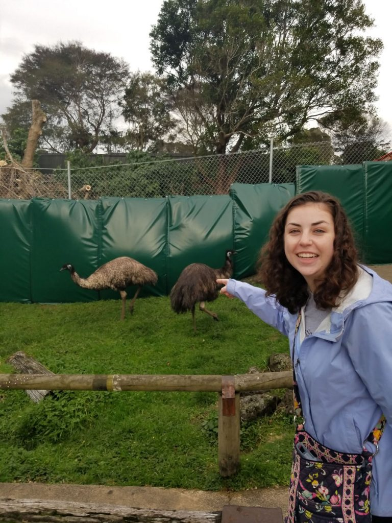 A USAC student at the Auckland Zoo pretending to touch an Emu