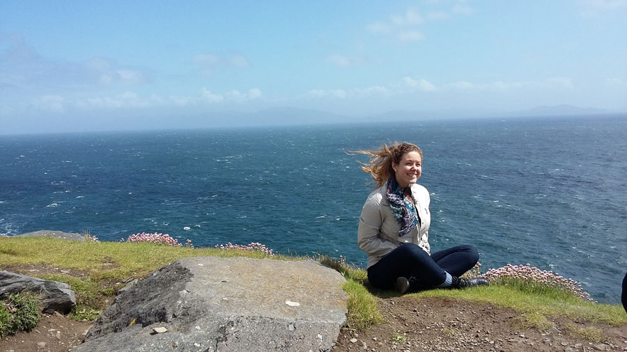 A student sits on the ocean side of Slea Head