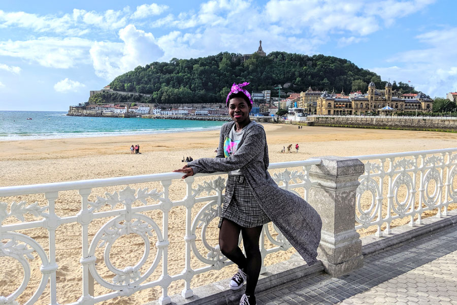 Student poses by the beach in San Sebastian, Spain during a study abroad with USAC