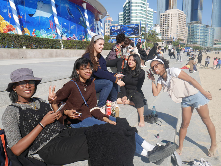 Students hang out at Busan Beach outside of the Busan Aquarium during a field trip with a study abroad in Seoul, South Korea