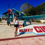 A student poses in front of the airplane museum in La Habana Cuba during a study abroad with USAC