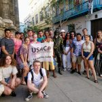 A group of students takes a photo in Cuba holding a USAC study abroad sign