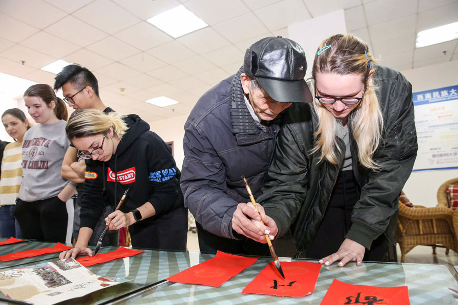 A student studying abroad in China learns how to write calligraphy