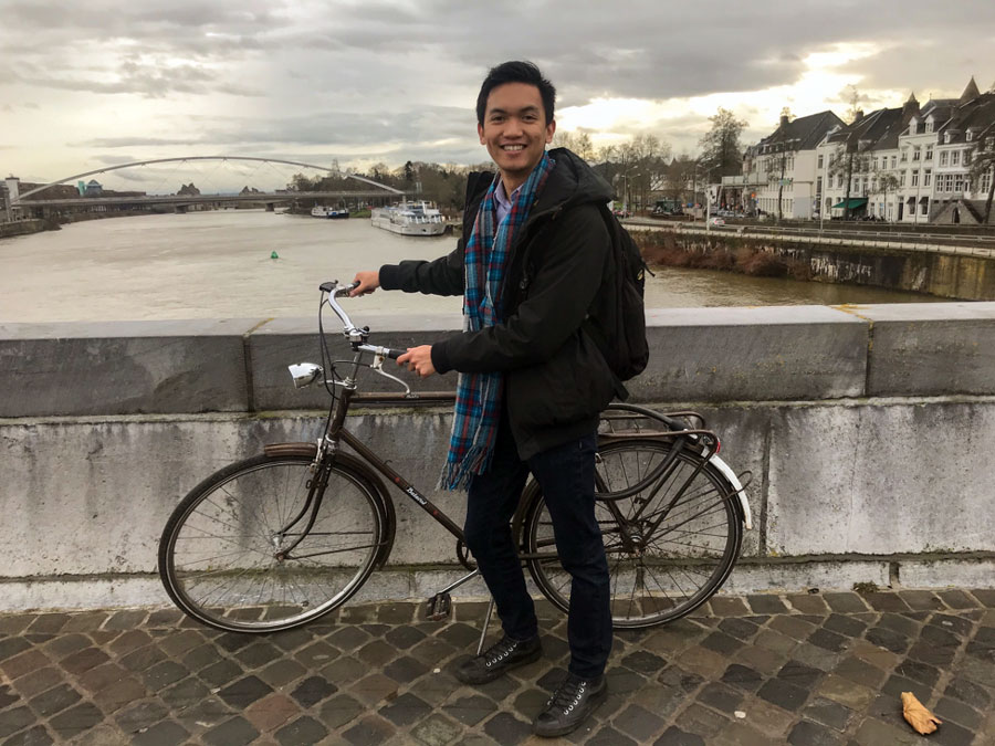 A student stops for a photo over the River Maas during a study abroad in Maastricht, The Netherlands