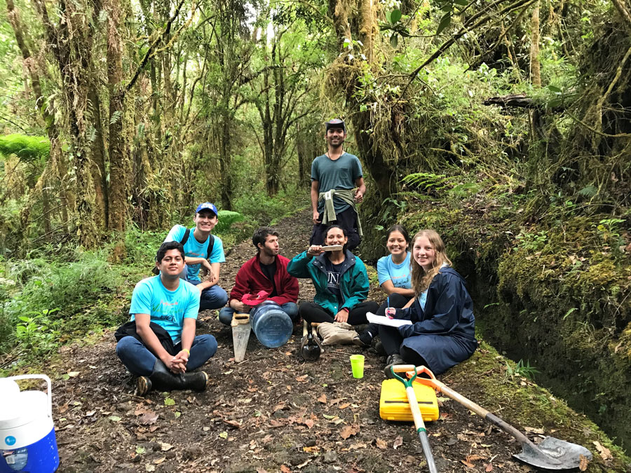 Students take a break in the Parque National Braulio Carrillo sign during a study abroad in Heredia, Costa Rica. Students volunteered to help enhance water resources in the park