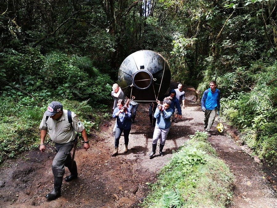 Students carry a water tank through Parque National Braulio Carrillo sign during a study abroad in Heredia, Costa Rica. Students volunteered to help enhance water resources in the park