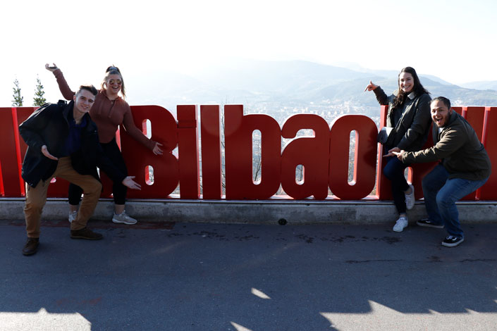 Students snap a photo in front of the Bilbao sign during a study abroad in Spain