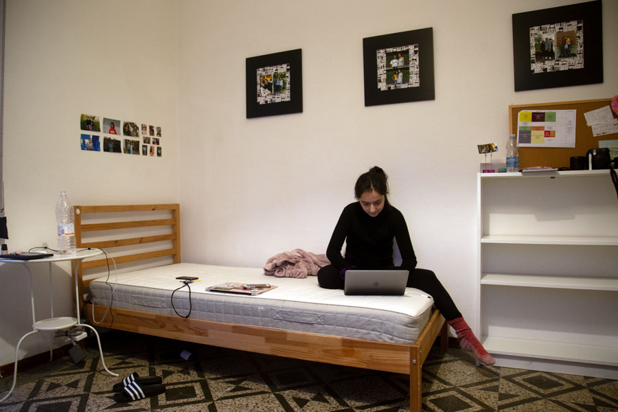 student studies on her bed during an online course