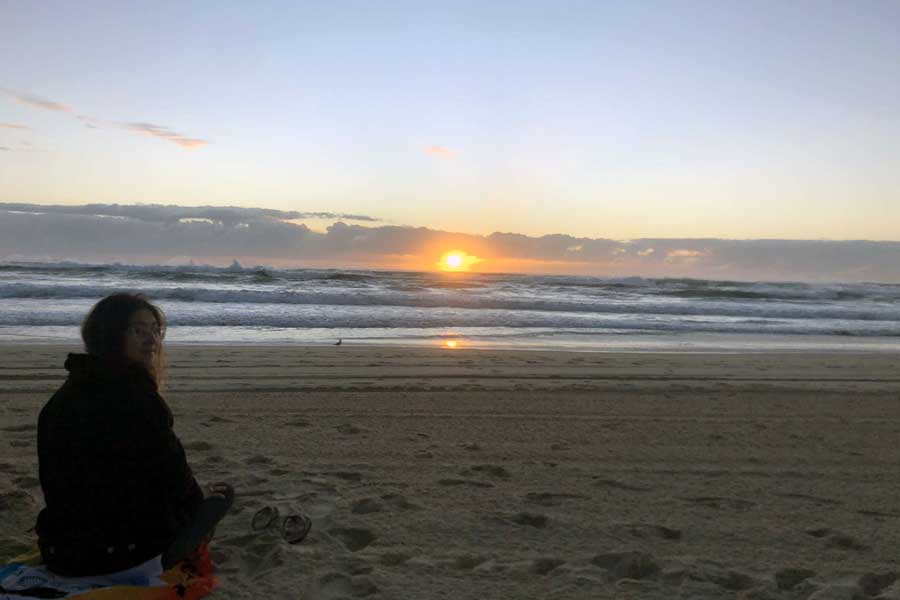A study abroad student sits on the beach in Australia