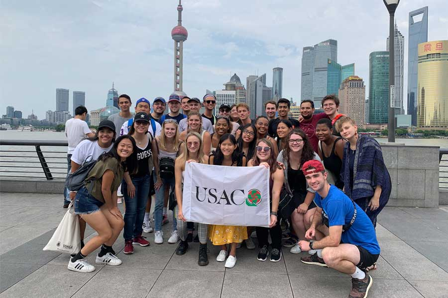 A group of students pose in front of the Bund in Shanghai, China during a study abroad with USAC