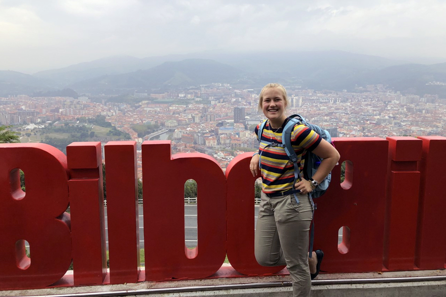 A Student poses in front of the Bilbao sign in Bilbao, Spain