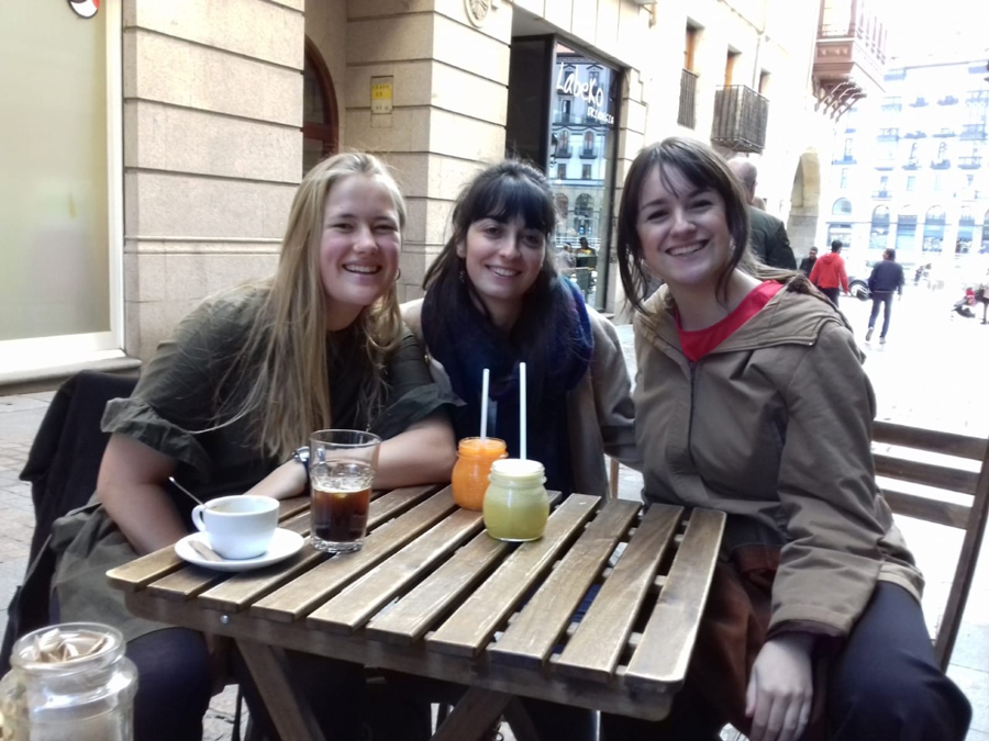 An American student studying abroad sits with two local girls from Bilbao, Spain in order to practice Spanish language.