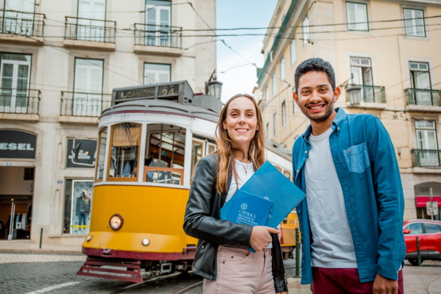 Two students pose by a cable car while exploring Lisbon, Portugal.