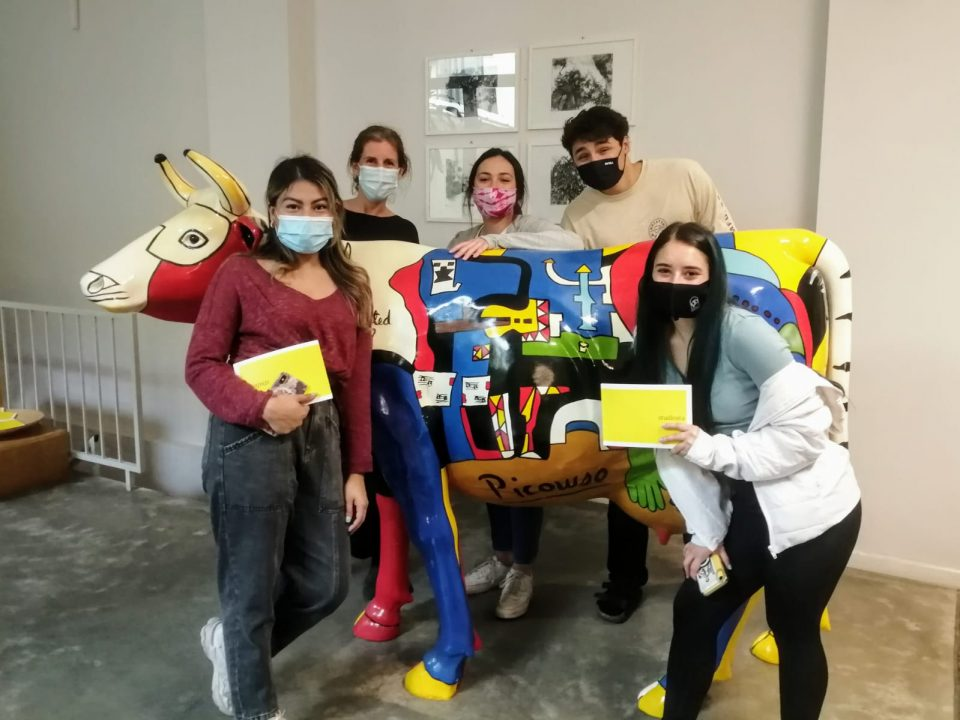 Students pose in front of a Picasso painting.